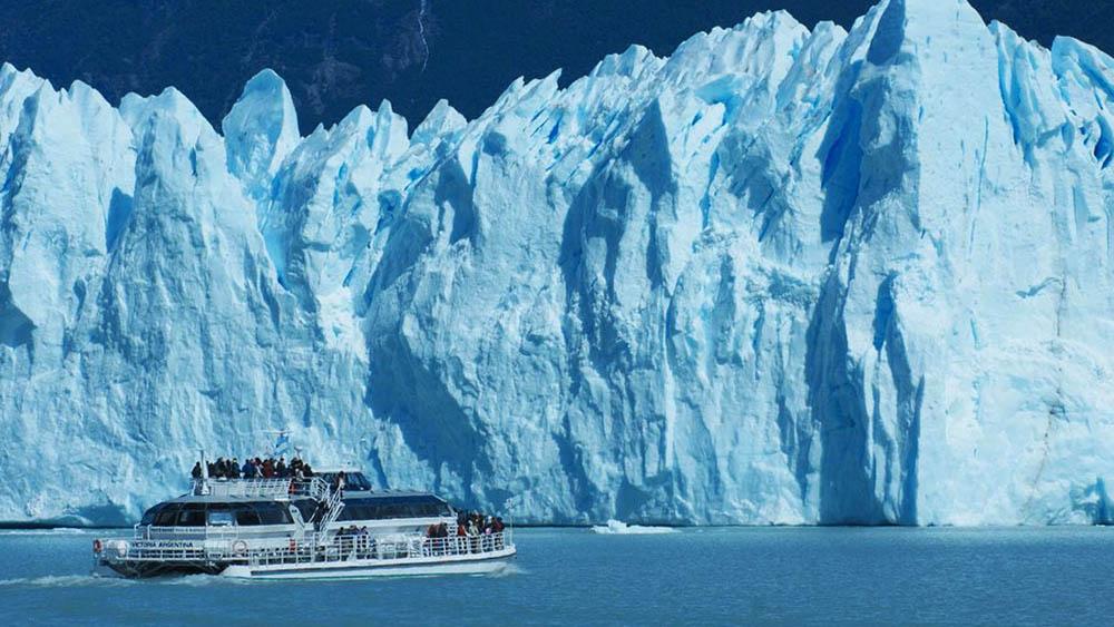 Barcos que fazem a travessia do lago ao lado dos paredões de gelo